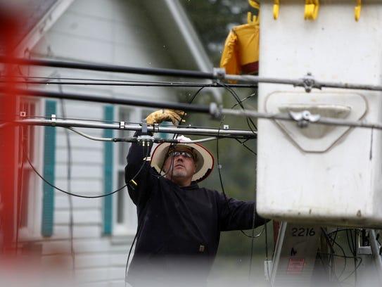 Lineman Heath Gebhardt works on a broken power pole