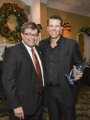 Jim Frey, left, 2016 associate president, of Pella, presents the 2016 Associate of the Year Award to Nick Smith, Keller Williams Realty.