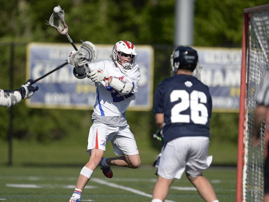 Fairport's Klay Stuver, left, scores on Pittsford goalie