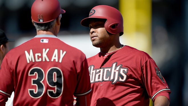 D-Backs' Yasmany Tomas is congratulated by first-base coach Dave McKay after his first hit in the majors late in the Diamondbacks' win over the Giants at AT&T Park on April 19, 2015 in San Francisco, California.