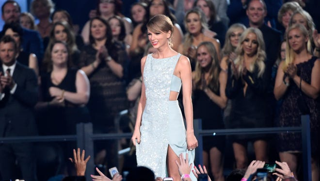 Taylor Swift walks on stage to accept the milestone award at the 50th annual Academy of Country Music Awards at AT&T Stadium on Sunday, April 19, 2015, in Arlington, Texas. (Photo by Chris Pizzello/Invision/AP)