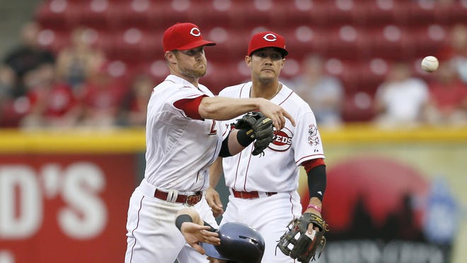 Cincinnati Reds shortstop Zack Cozart (2) sends a throw over to first base in a double play attempt.