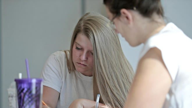 GED student Faith Rowland, 17, of Boone County completes a worksheet with help from her teacher, Erin McGlone, during a math lesson at Gateway Community & Technical College in Florence.