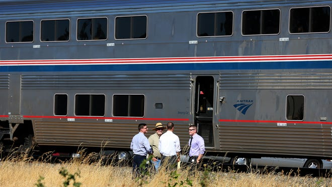 Members of the District Attorney's office examine the scene of a fatal pedestrian and Amtrak train crash, Thursday, August 6, 2015, in Salem, Ore.