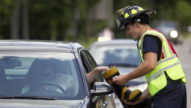 In this July 2015 photo, a Stevens Point firefighter collects donations from a driver to raise money for the Muscular Dystrophy Association. Marshfield city officials will not allow firefighters to do the same, citing safety concerns.