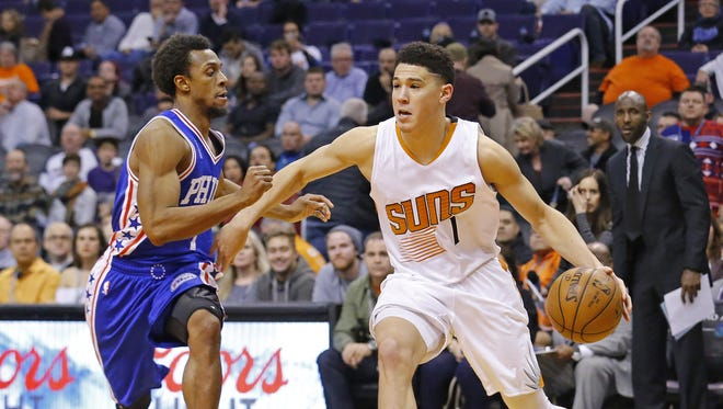 Phoenix Suns guard Devin Booker (1) works against Philadelphia 76ers Ish Smith in the second half of their NBA game Saturday, Dec. 26, 2015 in Phoenix, AZ.  The Suns lost 111-104.
