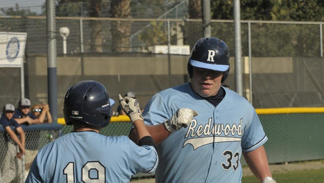 Redwood's Jace Chamberlin receives a high-five from teammate, Gunnar Haskill, against Bakersfield on Tuesday in a Central Section Division II semifinal game at Aaron Hill Field.