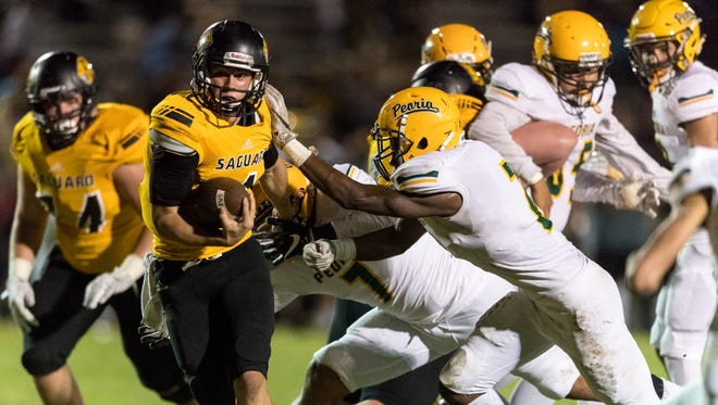 Saguaro's Max Massingale (#4) breaks a tackle from Peoria's Robert Duque (#7) and runs in for a touchdown in the first quarter of the Division 4A quarterfinal playoffs on Thursday, Nov. 10, 2016, at Saguaro High School in Scottsdale, Ariz.