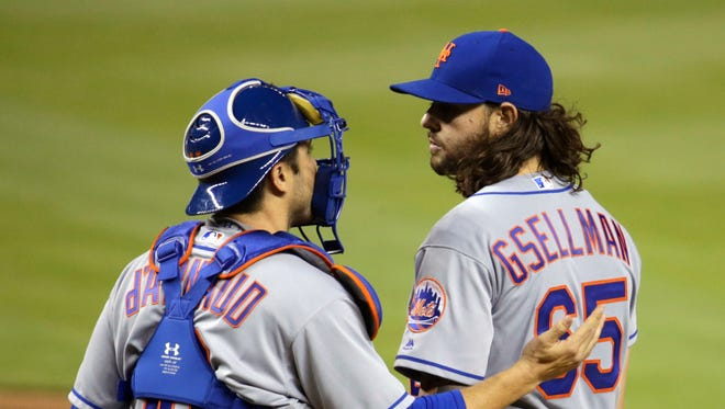 New York Mets catcher Travis d'Arnaud talks with starting pitcher Robert Gsellman (65) during the fifth inning of the team's baseball game against the Miami Marlins, Thursday, April 13, 2017, in Miami.