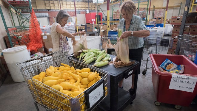 """Manna Food Pantry volunteers Lindsey Liders, left, and Caroline Halovsky sort through a new arrival of food donations to the Manna warehouse on Monday, June 19, 2017. Members of the Pensacola Police Department and the Escambia County Sheriff's Office are on a """"doughnut strike"""" collectively vowing not to eat a single doughnut until 2.5 tons of food has been donated to fight hunger in the local area. The food will go to Manna Food Pantries, a nonprofit that feeds needy families in Escambia and Santa Rosa counties."""