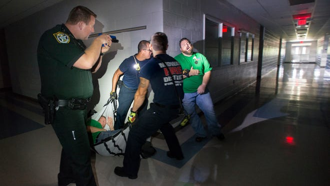 Santa Rosa County Deputy Mason Doggette, left, provides protection as Midway Fire District firefighter/paramedics evacuate victims from a darkened building during an active shooter training exercise held by Santa Rosa County authorities at Woodlawn Beach Middle School in Gulf Breeze on Monday, July 17, 2017.