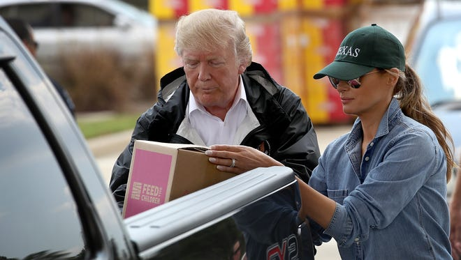 President Trump and first lady Melania Trump load emergency supplies into the back of a pickup truck for  residents impacted by Hurricane Harvey while visiting the First Church of Pearland September 2, 2017 in Pearland, Texas.
