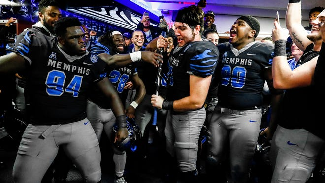 Memphis offensive lineman Gabe Kuhn (middle) prepares to break a slab of concrete with the teams player of the game sledge hammer after defeating SMU in Memphis, Tenn., Saturday, November 18, 2017.