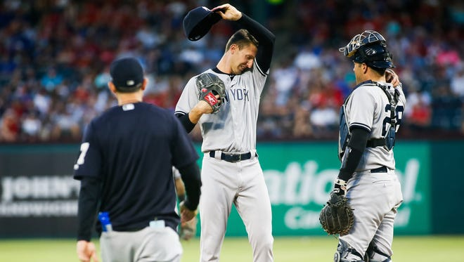 New York Yankees relief pitcher Chasen Shreve (45) wipes his brow as manager Aaron Boone (17) walks to the mound to change pitchers in the sixth inning against the Texas Rangers at Globe Life Park in Arlington.