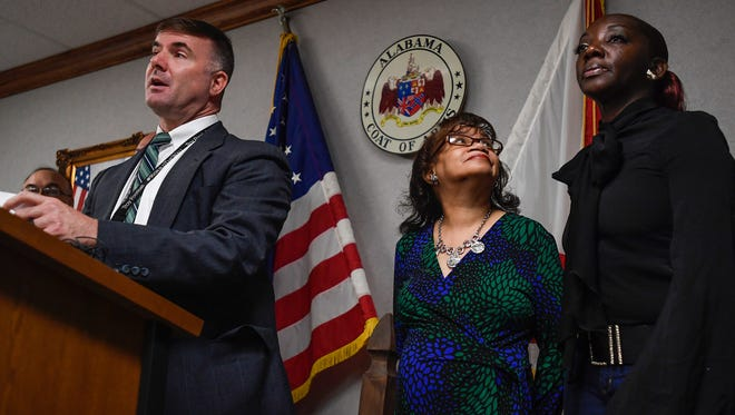Aieda Harris, mother of murder victim Edward Reeves, looks up at Felicia Webster, mother of murder victim Kendrick Stokes, as Lt. Shawn Loughridge, of the State Bureau of Investigation, asks for help in the double murder investigation during a news conference at the ALEA headquarters in Montgomery, Ala. on Friday May 25, 2018.