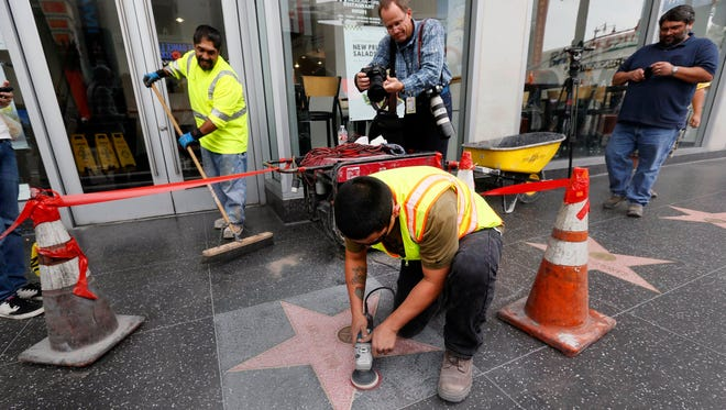 A work crew finishes up cleaning the Bill Cosby star on the Hollywood Walk of Fame after it was defaced by graffiti in Los Angeles on Friday, Dec. 5, 2014. The Hollywood Chamber of Commerce wrote in a statement that it hoped people upset with Cosby would find different ways to express themselves than vandalism.