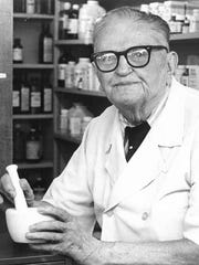 (Original caption Sept. 11, 1980) - Like Old Times - S.G. Denny of Wichita Falls, pioneer druggist, dons his pharmacy coat and holds a mortar and pestle, indispensable tools  of the early-day pharmacist, at his 88th birthday celebration here Wednesday afternoon. Founder in 1922, of Brook and Eighth Drug, where he worked until his retirement three years ago, Denny was (sic) honored guest at a reception given at the drugstore by Mr. and Mrs. Johnnie Braun, present owners.
