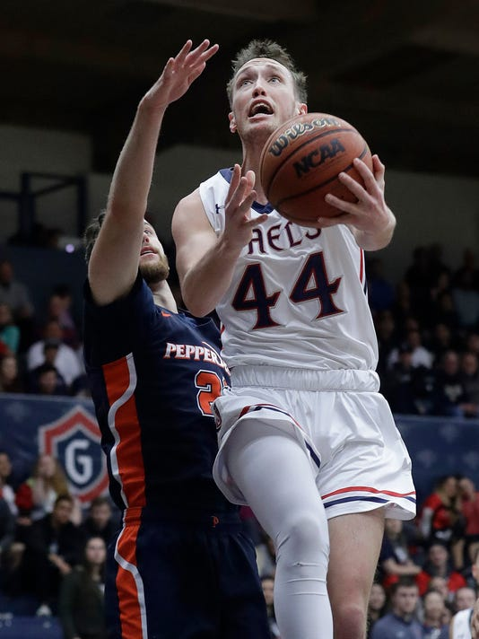 Saint Mary's guard Cullen Neal (44) shoots in front of Pepperdine guard Knox Hellums during the first half of an NCAA college basketball game in Moraga, Calif., Thursday, Feb. 22, 2018. (AP Photo/Jeff Chiu)