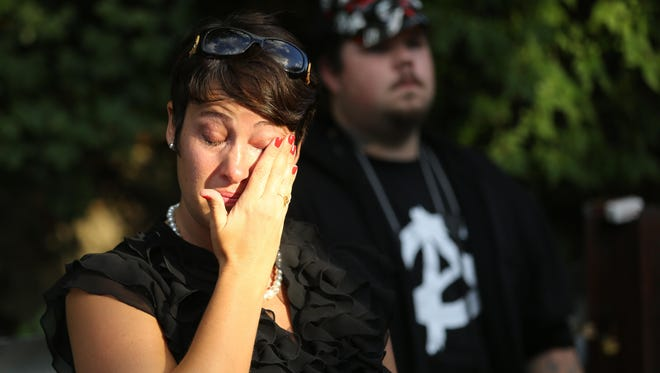 """Jennifer Rice wipes away tears as Samuel DuBose's family members speak at the place where DuBose was shot and killed by a UC police officer. Rice says that she was friends with Russell Rogers, who died while in the custody of the Hamilton Police Department in 1997. """"I know what their family is going through,"""" she said."""