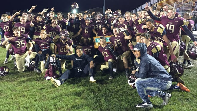Licking Heights players celebrate with the Battle for Broad Street plaque following Friday's 31-22 victory against Watkins Memorial.