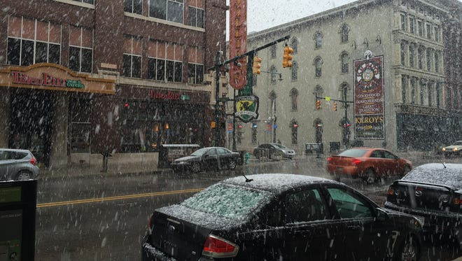 Snow falls on South Meridian Street just outside the main entrance of The Indianapolis Star Downtown on Saturday, Nov. 21.