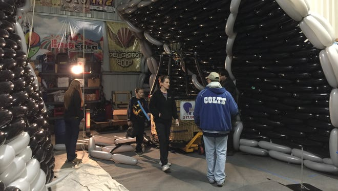 """Volunteers help build a giant balloon sculpture of a TIE fighter from the original """"Star Wars"""" movie that was designed by Indianapolis balloon artist Brian Getz. The sculpture was recently assembled at Indianapolis Metropolitan Airport in Fishers."""