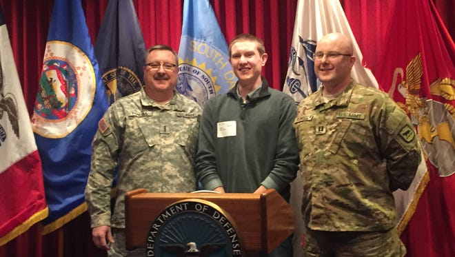 Colin Powell (center) poses with his father Jess Powell (right) and grandfather Jay Powell (left) after his swearing in ceremony at the Sioux Falls Military Entrance Processing Station on Friday.