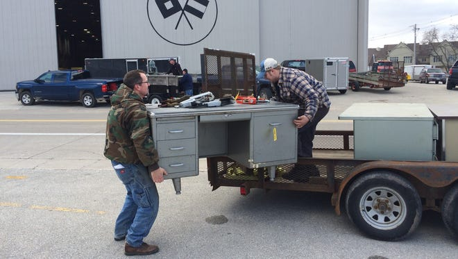 Darrin Duffeck of Algoma helps Bill Zasada of Green Bay load up one of six large desks Zasada purchased from the Palmer Johnson Yachts auction for $1 each.