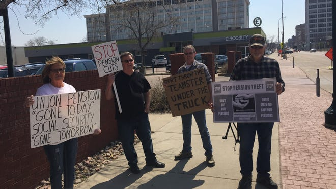 Four of the two dozen protesters who walked between the offices of Sen. Mike Rounds and Rep. Kristi Noem on Thursday to call attention to impending cuts to the Central States Pension Plan.