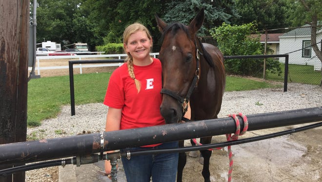 Morgan Stoner, 19, stands with her horse Duke after washing him off following the Horse Speed Class competition Tuesday at the Marion County Fair.