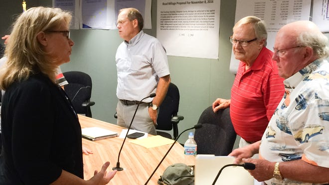 State Rep. Lana Theis (left) discusses roads with Hamburg Township Trustee Bill Hahn (right) and Treasurer Allen Carlson (center right), as Supervisor Pat Hohl (center left) speaks with constituents after a special public summit on the condition of township roads.