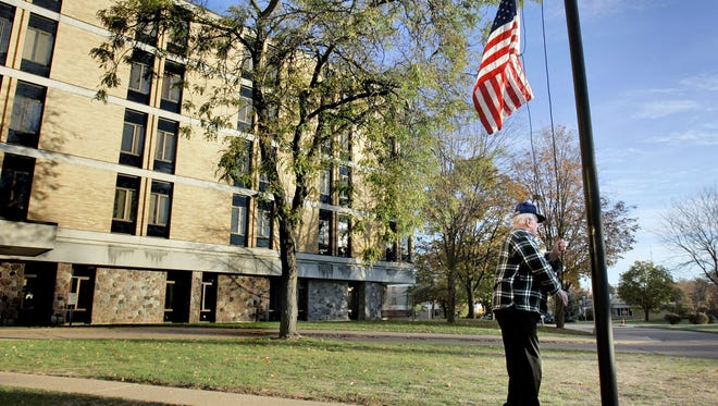 A World War II veteran raises the flag at the Wisconsin Veterans Home in King in this 2006 file photo.