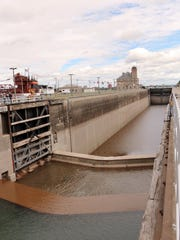 In this Monday, Aug. 3, 2015 photo, the MacArthur Lock is shown under repair in Sault Ste. Marie, Mich. Officials say one of the navigational locks at Sault Ste. Marie is being shut down because of mechanical problems. The Soo Locks raise and lower ships traveling between Lake Superior and Lake Huron through the St. Marys River. It's a crucial link for vessels hauling iron ore, coal and other bulk cargo. (Angela Kipling/The Evening News via AP)