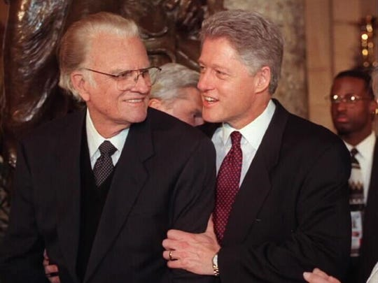President Clinton embraces Rev. Billy Graham on Capitol Hill Monday Jan. 20, 1997 during an inaugural luncheon after the president was sworn in for a second term. (AP Photo/Joyce Naltchayan/Pool)
