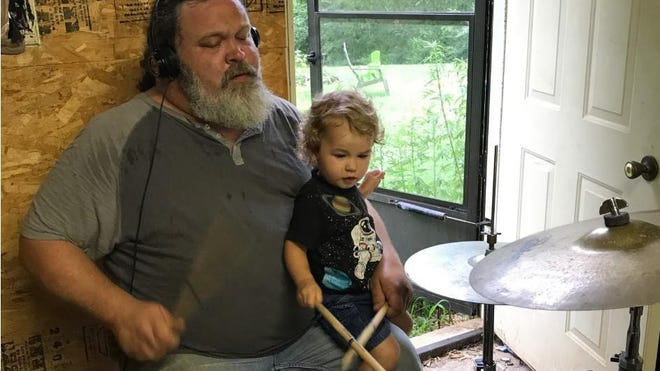 Alan Keever is shown playing the drums with his son, Oliver.