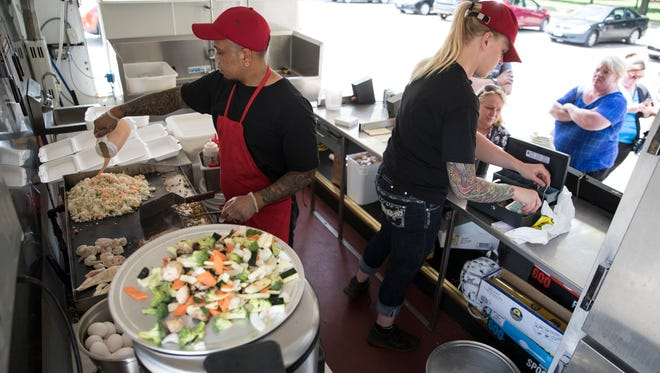 Jay Jelantik, left, prepares food while his wife, Jamie, takes orders in their Hometown Hibachi mobile restaurant during their first day serving customers in Yoctangee Park this summer.