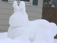 A giant snow Easter bunny sculpture sits on a front