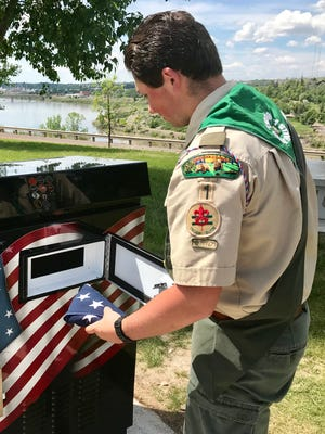 Eagle Scout candidate Sean Lynch deposits the first flag in the flag box at Veterans Memorial Park.
