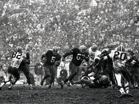 Green Bay Packers halfback Paul Hornung (5) follows guard Fuzzy Thurston (63) upfield against the Cleveland Browns during the NFL championship game at Lambeau Field on Jan. 2, 1966. It was Hornung?s last great game with the Packers. He had 18 carries for 105 yards and a touchdown. Browns linebacker Jim Houston (82) is at left. The Packers won 23-12. » This is one of almost 300 rarely and never-seen Green Bay Press-Gazette photos from the 1965 NFL championship game at Lambeau Field. See them all in four photo galleries at www.packersnews.com.  Press-Gazette Media archives Green Bay Packers halfback Paul Hornung (5) follows guard Fuzzy Thurston (63) upfield against the Cleveland Browns during the NFL championship game at Lambeau Field on Jan. 2, 1966. Browns linebacker Jim Houston (82) is at left. The Packers won 23-12. Press-Gazette archives