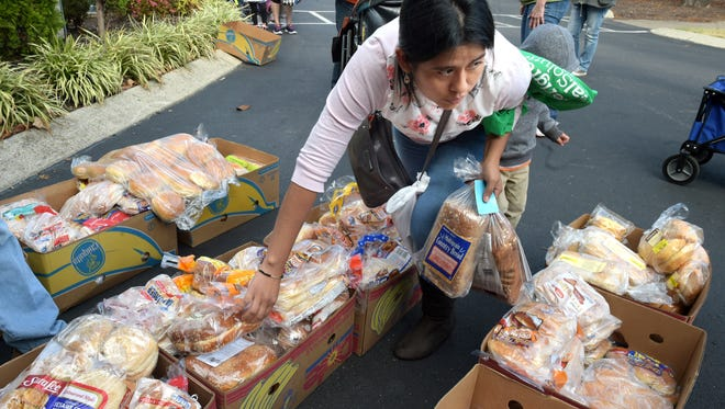 Sonia Cornelio picks out bread for her family during a perishable food drive at Lady of Guadalupe Catholic Church on Nolensville Road on Friday, Oct. 21, 2016. It's families like the Cornelios who make up most of Second Harvest Food Bank's clientele: the working poor.