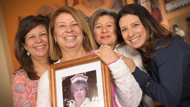 Christina Calderon, second from left, holds a portrait of her late mother and New Mexico State nursing alumna Margaret Pacheco near the Nursing Wall of Excellence inside the NMSU College of Health and Social Services building. Calderon is joined by her sisters Martha Rivera, left, and Estela Heredia, second from right. Pacheco's grandaughter, Amy Lopez, appears at right. All four women are NMSU alumni, and Calderon, Rivera and Lopez are all nurses.