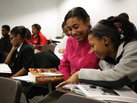 Detroit Edison Public School Academy students Mia Grady, center, and Tamia Cooper, right, go over lessons during an Africana studies