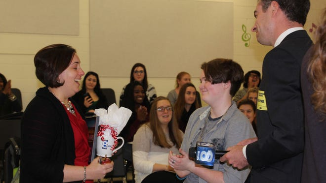 Carrie Zugelder reacts when presented with her Golden Apple Award by her student Elizabeth Monroe and News 8 anchor Adam Chodak (provided photo)