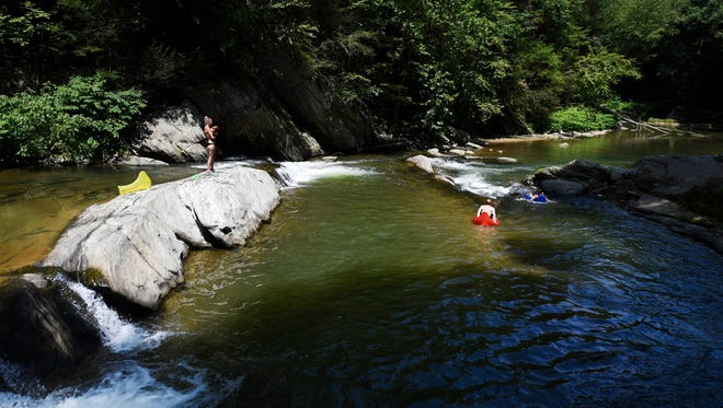From left Allysa Huster, Alex Leffler, and Amanda Hull, all of Red Lion, cool off at a swimming hole on Muddy Creek along the Mason-Dixon Trail in Peach Bottom Township.
