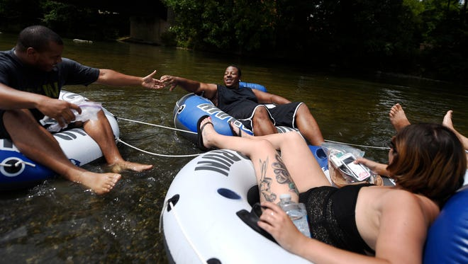 From left Charles Crewsaw of Lemoyne, Dwayne Connor or Harrisburg and Nikki Frye of Harrisburg begin a tubing adventure on Yellow Breeches Creek at Messiah College in Upper Allen Township.