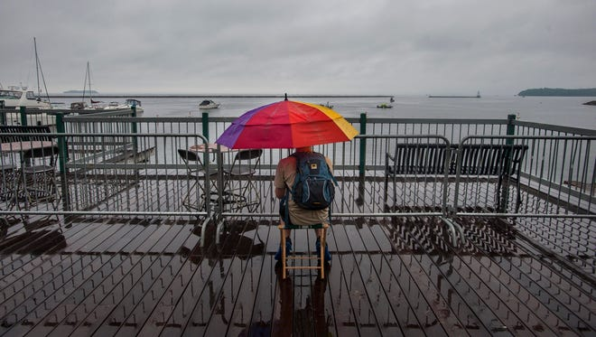 A spectator waits on the waterfront boardwalk for the rain delay to end and the Wings Over Vermont air show to begin in Burlington on Saturday, August 13, 2016.