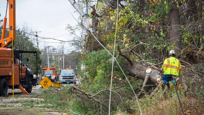 Crews work to clear wind storm damage that closed Route 2A in Colchester on Monday, October 30, 2017.