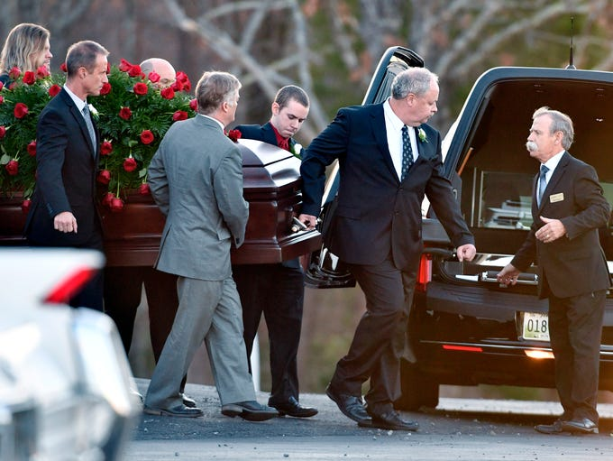 Pallbearers carry the casket following the funeral