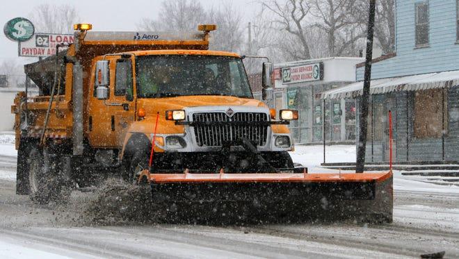 A snow plow clears west Kearney Street on Wednesday, March 4, 2015.