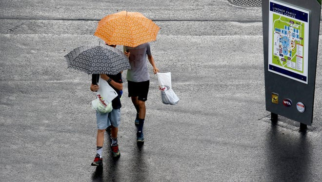Tennis fans try to stay dry as a storm stops matches during the Western and Southern Open at The Lindner Family Tennis Center in Mason Monday. Rain has been a common theme throughout this year's tournament.